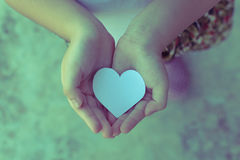 Children hands holding small model of heart and family Royalty Free Stock Images