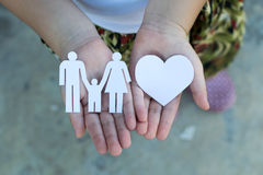 Children hands holding small model of heart and family , concept Stock Photos