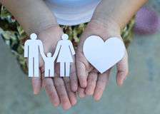 Children hands holding small model of heart and family Royalty Free Stock Photo