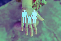 Children hands holding small model of heart and family Stock Photo