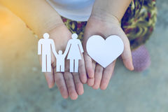 Children hands holding small model of heart and family Royalty Free Stock Photography
