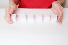 Children hands and row of six small paper cubes Royalty Free Stock Photography