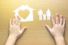 Children hands with small model of house and family Royalty Free Stock Image