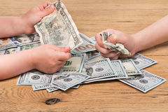 Children hands squeeze money. Children play real money on the wooden floor by squeezing them with their hands, close-up Royalty Free Stock Image