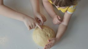 Children hands stroking and crumpling the dough on the table. Top view stock video footage