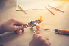 Children hands with Toy iron plane. Metal constructor with screwdrivers. Dream, play and create royalty free stock images