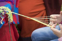 Needlework. Children hands weave a yarn from a yarn. Weaving belts is one of the popular and accessible types of needlework Royalty Free Stock Images