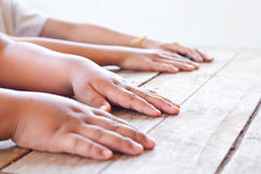 Children hands on wood table. Royalty Free Stock Photos