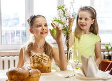 Children hang easter egg on cherry branch. Royalty Free Stock Photography