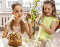 Children hang easter egg on cherry branch. Royalty Free Stock Photo