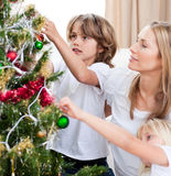 Children hanging Christmas decorations. With their mother in the living-room Royalty Free Stock Image