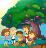 Children hanging out under the apple tree Royalty Free Stock Images