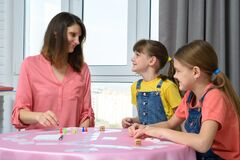 Children happily looked at mom playing board games