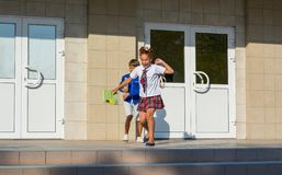 Children happily run from school after the end of lessons. Laughing schoolchildren - a girl and a boy are happily running stock photography