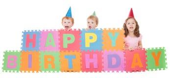 Children with happy birthday kids sign. Three children holding happy birthday sign. Isolated on white Stock Photos