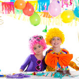 Children happy birthday party with clown wigs. And chocolate cake Royalty Free Stock Photography