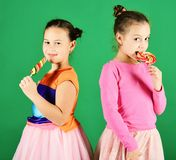 Children with happy faces pose with candies on green background. Treatment and sweets concept. Girls eat big colorful sweet caramels. Sisters with round and stock images