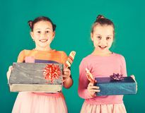 Children with happy faces pose with candies and presents. On green background. Girls eat big colorful sweet caramels opening gifts. Confectionery concept stock image