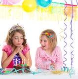 Children happy girls blowing birthday party cake