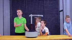 Children have an experiment with electromagnetic fountain. The boys put metal ring on the equipment and the ring jump up. Fascinating experiments with physics stock footage