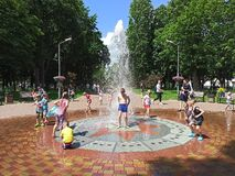 Children have a fun with city fountains during summer heat
