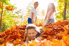 Children have fun dragging girl laying on ground Royalty Free Stock Photos
