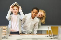 Children have fun in elementary school. In class in front of the empty blackboard royalty free stock photo
