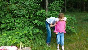Children have fun in the forest on the shore of a large lake. The children ate fruit. They have a good mood. They are having fun. Evening in the summer forest stock video