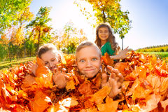 Children have fun laying on the ground with leaves Stock Photos