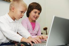 Children have fun playing games on laptop computer Royalty Free Stock Photos