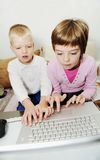 Children have fun playing games on laptop computer Royalty Free Stock Image