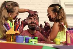 Free Children Have Fun With Their Father. Girls Drawing On Man Face Skin With Colorful Paints Stock Photography - 119295802