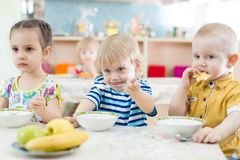 Kids have lunch in kindergarten or day care centre royalty free stock images
