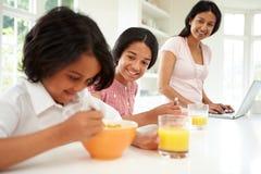 Children Having Breakfast With Mother Before School Stock Photo