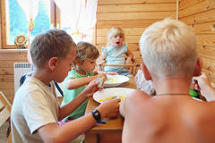 Children having dinner behind table Stock Photos