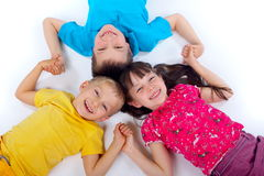 Children having fun. Children lying on backs and liking arms together, having fun Stock Image