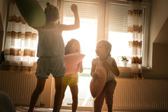 Children having fun on the bed and have a fight with pillows. stock photography