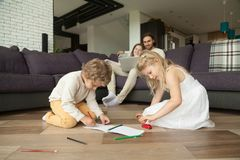 Children having fun drawing together, happy family leisure home. Children boy and girl having fun drawing on warm house floor while parents using laptop, kids royalty free stock photography