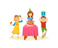 Children having fun in a festive evening at birthday party. Concept - fun children. Young children are happy, having fun, playing on maracas, girl blowing cake Stock Photos