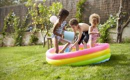 Children Having Fun In Garden Paddling Pool Royalty Free Stock Photo