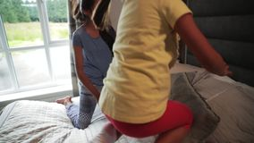 Children Having Fun on Holiday. Slow motion shot of two sisters bouncing on a bed while on holiday stock video footage