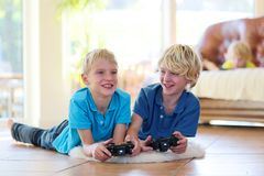 Children having fun at home. Group of kids twin teenage brothers having fun after school day playing video game, holding joysticks in hands, lying cozy on tiles Stock Photos