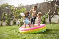 Free Children Having Fun In Garden Paddling Pool Stock Images - 85340144