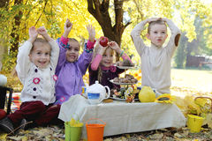 Children having fun on picnic under autumn leaves. Happy children having fun on picnic under autumn leaves Royalty Free Stock Photos