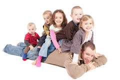 Children having fun playing with dad. Children sitting on mans back on floor. Isolated Royalty Free Stock Images