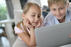 Children having fun playing on tablet at home Royalty Free Stock Image