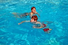 Children having fun in the pool Stock Images