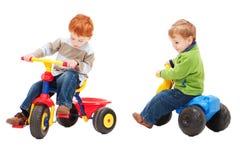 Children having fun riding on kids bikes. Two boys playing on three wheel bikes. Isolated on white Stock Photography