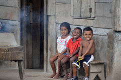 Children having fun. SAUPUKA, NICARAGUA - JULY 8, 2015:  Two unknown Nicaraguan boys and one unknown Nicaraguan girl sit on their porch playing under cover Royalty Free Stock Photography