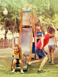 Children having fun on slide at playground Royalty Free Stock Images